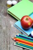 Bücher, Bleistifte und ein Apfel Lizenzfreie Stockfotos