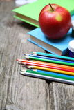 Bücher, Bleistifte und ein Apfel Stockbild