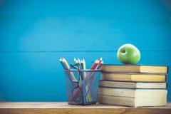 Bücher, Briefpapier und ein grüner Apfel auf dem Schreibtisch Stockbilder
