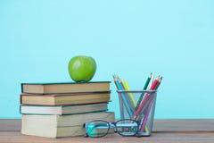 Bücher, Briefpapier und ein grüner Apfel auf dem Schreibtisch Lizenzfreies Stockfoto