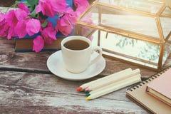 Bücher, bunte Bleistifte und Tasse Kaffee auf dem alten Holztisch im Freien im Park Stockbild