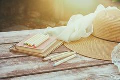 Bücher, bunte Bleistifte und weiblicher Hut auf dem alten Holztisch im Freien im Park Stockbilder