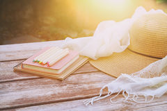 Bücher, bunte Bleistifte und weiblicher Hut auf dem alten Holztisch im Freien im Park Lizenzfreie Stockfotos