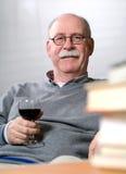Bücher des älteren Mannes Lesemit einem Glas Wein Stockfoto