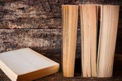 Bücher, die in Folge nahe bei dem Buch auf einem Holztisch stehen Stockbilder