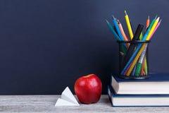 Bücher, ein Apfel, bunte Bleistifte in einem Fall und ein Papierflugzeug Auf einem dunklen Hintergrund Das Konzept der Bildung Lizenzfreie Stockbilder