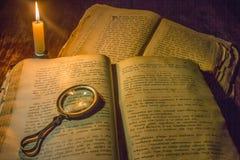 Bücher eines offene alte Gebets und eine Lupe auf seinen offenen Seiten unter dem Licht einer Kerze Lizenzfreie Stockfotos