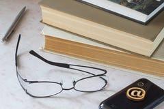 Bücher, Gläser, Stift, Telefon auf Tabelle Stockbilder