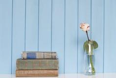 Bücher häufen und Weißrose in der Flasche an Stockbild