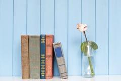 Bücher häufen und Weißrose in der Flasche an Stockfotografie