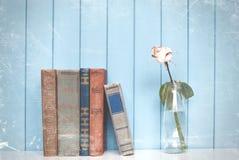 Bücher häufen und Weißrose in der Flasche an Stockfoto
