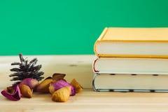 Bücher mit dem rosafarbenen Blumenblatt auf einem hölzernen Schreibtisch Stockfoto
