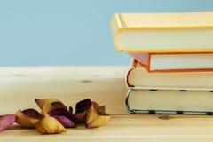 Bücher mit dem rosafarbenen Blumenblatt auf einem hölzernen Schreibtisch Stockfotos