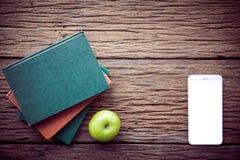 Bücher, Mobiltelefon und ein grüner Apfel auf dem hölzernen Schreibtisch Lizenzfreies Stockfoto