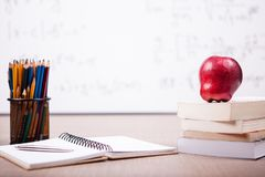 Bücher, Notizbuch und Bleistifte auf Tabelle mit einem unscharfen weißen Brett Lizenzfreies Stockfoto