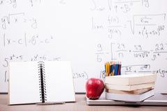Bücher, Notizbuch und Bleistifte auf Tabelle mit einem unscharfen weißen Brett Lizenzfreies Stockbild