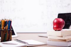 Bücher, Notizbuch und Bleistifte auf Tabelle mit einem unscharfen weißen Brett Stockfotos