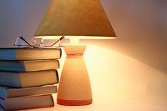 Bücher, Schauspiele und Lampe stockfotografie