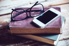 Bücher, Smartphone und Gläser Stockfotos