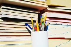 Bücher, Stifte, Bleistifte und Notizbücher, bunter Hintergrund Lizenzfreie Stockfotos