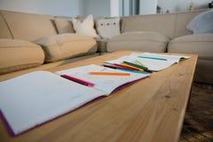 Bücher und Bleistifte auf einer Tabelle im Wohnzimmer Lizenzfreie Stockfotografie
