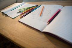 Bücher und Bleistifte auf einer Tabelle im Wohnzimmer Lizenzfreie Stockfotos