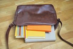 Bücher und Bleistifte im ledernen Rucksack Lizenzfreie Stockfotos