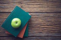 Bücher und ein grüner Apfel auf dem Schreibtisch Stockfoto