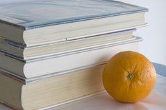 Bücher und eine Orange. Stockfoto