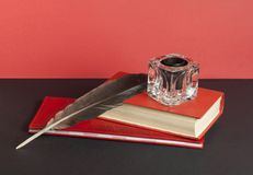 Bücher und Federkiel mit Tintenfaß auf schwarzer Tabelle auf Hintergrund der roten Wand Freiexemplarraum getrennte alte Bücher Lizenzfreie Stockfotos