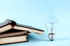 Bücher und Glühlampe auf blauem Hintergrundabschluß oben Lizenzfreie Stockfotografie