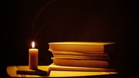 Bücher und Kerze Feuer und Rauch stock footage