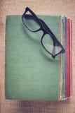 Bücher und Lesebrille auf Weinlese Leinwandhintergrund mit Inst Lizenzfreie Stockfotos