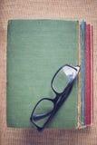 Bücher und Lesebrille auf Weinlese Leinwandhintergrund mit Inst Lizenzfreie Stockfotografie