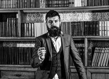 Bücher und Literatur Sprecher mit ruhigem Gesicht steht im Weinleseinnenraum Bärtiger Mann in der eleganten Klage nahe Bücherschr lizenzfreie stockbilder