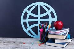 Bücher und Notizbücher, appleand Bleistifte in einer Wanne, auf einem dunklen Hintergrund mit einem Bild eines Landes mit Meridia Lizenzfreie Stockfotografie