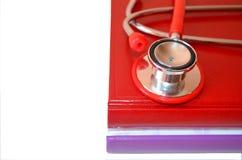 Bücher und rotes Stethoskop Stockbilder