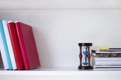 Bücher und sandglass auf dem weißen Regal Lizenzfreies Stockfoto