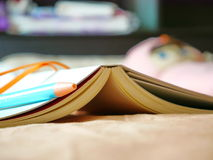 Bücher und Stifte werden auf das Bett gesetzt Stockbild