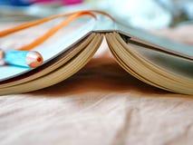 Bücher und Stifte werden auf das Bett gesetzt Stockfotos