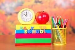 Bücher, Wecker, roter Apfel, Bleistifte und Griffe Lizenzfreie Stockfotos