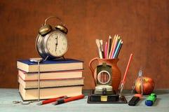 Bücher, Wecker, Schulbedarf und ein Apfel Lizenzfreie Stockfotos