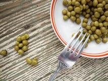 In Büchsen konservierte grüne Erbsen in der Platte Lizenzfreies Stockbild