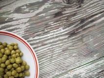 In Büchsen konservierte grüne Erbsen in der Platte Lizenzfreie Stockfotografie