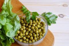In Büchsen konservierte grüne Erbsen, Kopfsalatblatt Stockfotos