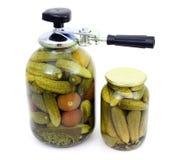 In Büchsen konservierte Nahrung und die Maschine zum Versiegeln in Büchsen konservierte Nahrung Stockfotos