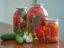 In Büchsen konservierte Tomaten und Gurken in den Glasgefäßen lizenzfreie stockbilder