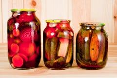 In Büchsen konservierte Tomaten und Gurken in einem Glasgefäß auf einem hölzernen Hintergrund stockfotos