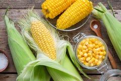 In Büchsen konservierter Zuckermais im Glasgefäß-, frischem und gekochtemmais auf Pfeilern, Salz lizenzfreie stockbilder