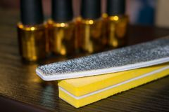 Büffelleder und Nagelfeile auf dem Hintergrund von Flaschen Nagellack lizenzfreie stockfotografie